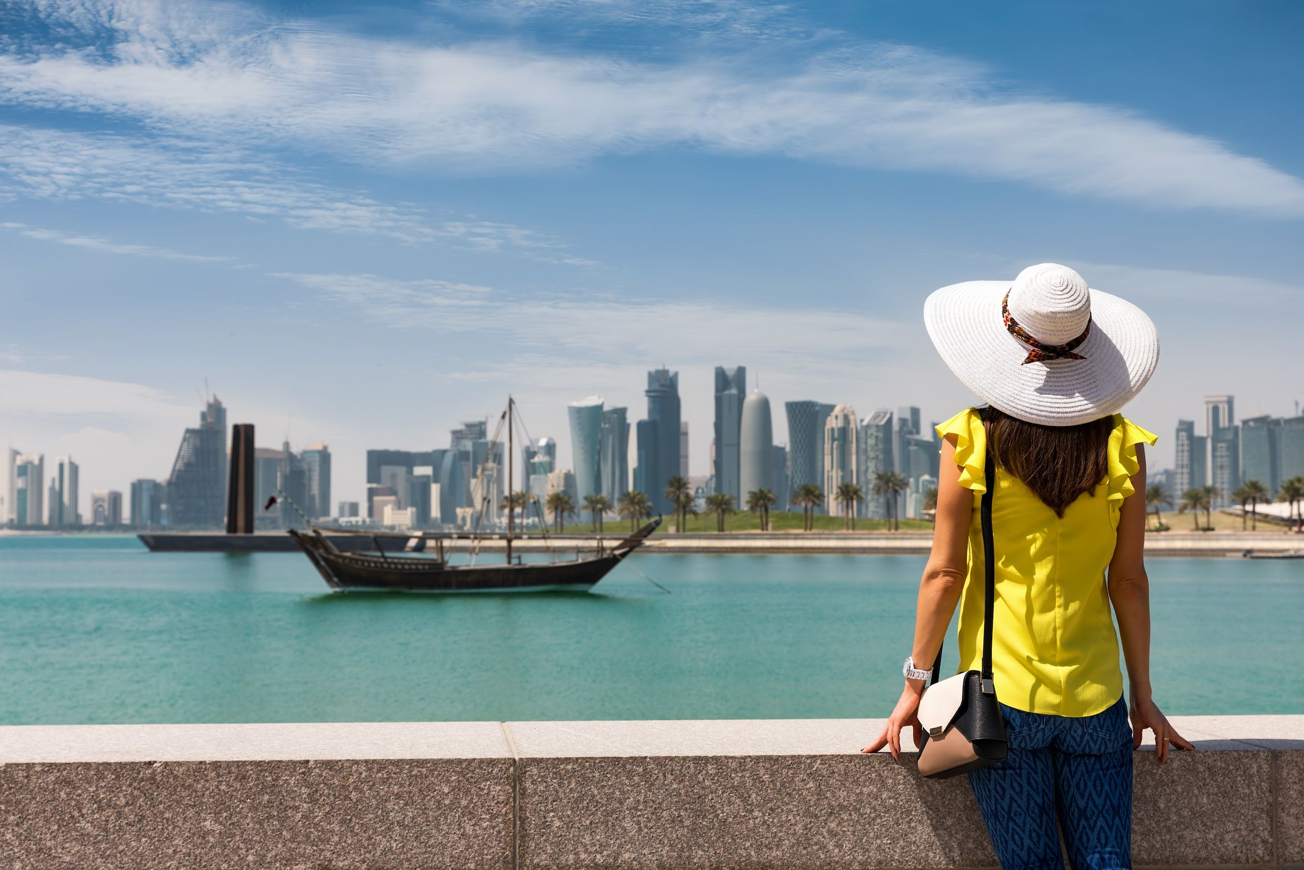 Traveller woman with sunhat enjoys the view to the skyline of Doha, Qatar