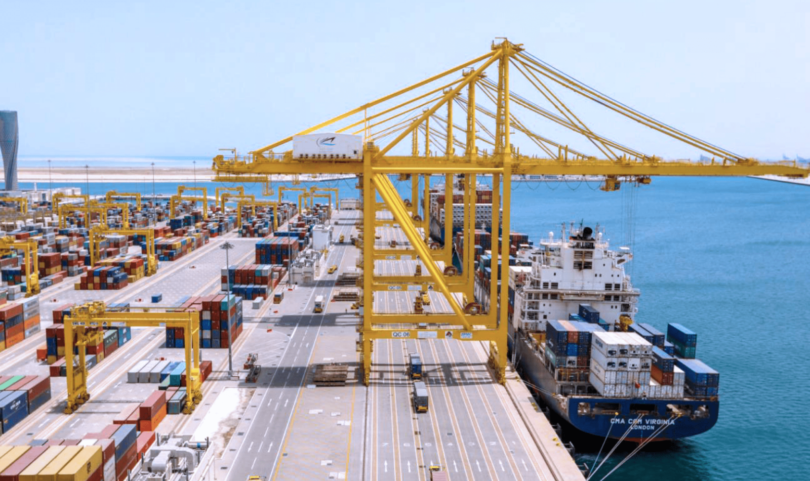 Hamad Port cargo loading, large yellow container cranes placing containers on cargo ships