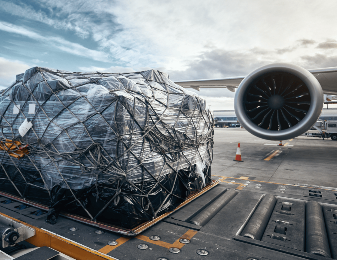 Packaged air cargo secured with ropes, sitting next to airplane wing on a runway