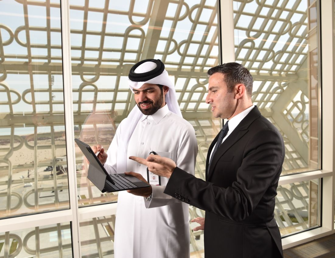 Two businessmen, one in a suit and one in traditional Arabic clothing, standing together discussing while pointing at a computer screen