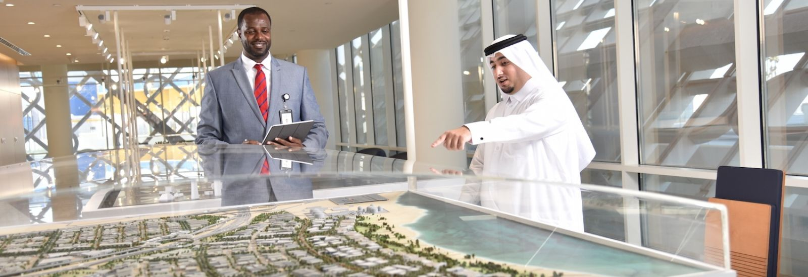 Two men, one in a suit and one in traditional Arabic clothing, pointing at a 3-D map of the Qatar Free Zones