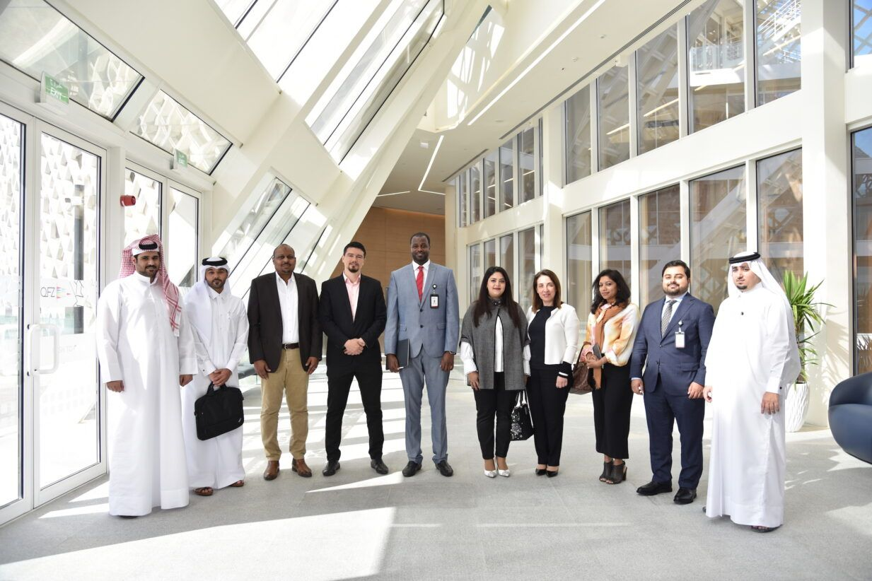 Qatar Free Zones Authority's diverse investor support team, standing in line smiling at a camera