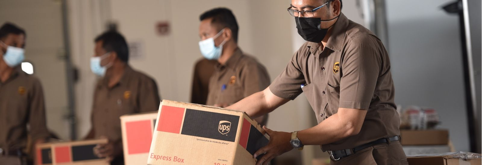 UPS packaging facility, workers in brown uniforms with masks handling packages