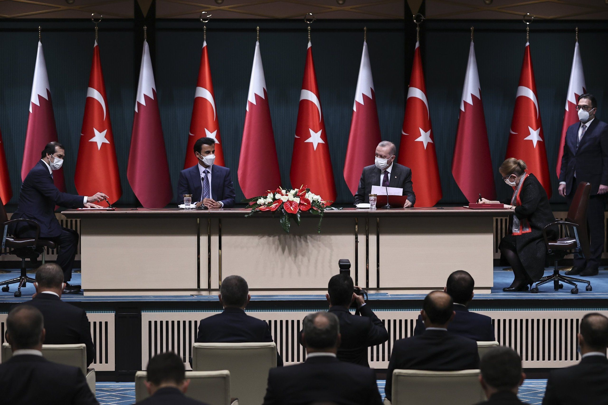 Members from Turkish and Qatari government at a press conference, signing trade documents in front of country flags